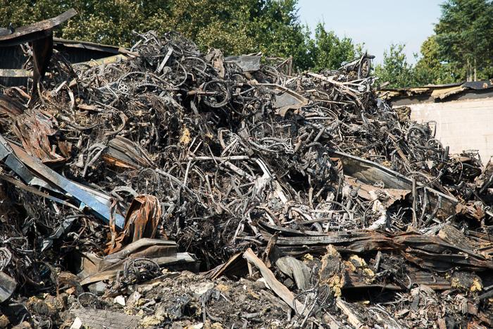 Nunspeet - Een dag na de brand bij Stella, waar een groot aantal fietsen en accu's verbrand zijn, Is het gebied afgezet als 'Plaats Delict'. De brandweer heeft de accu's in een drietal containers gestopt en deze vol water gepompt.